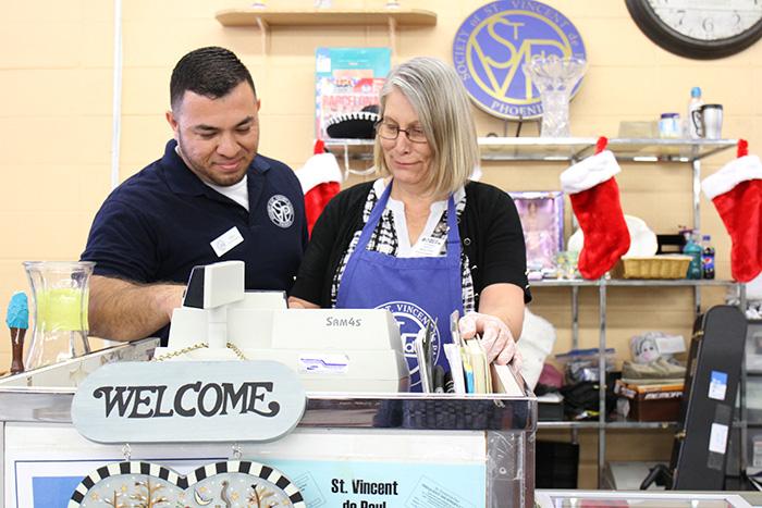 Mesa Thrift Store manager Alex Loya trains Encore Fellow Josie on cashier duties.