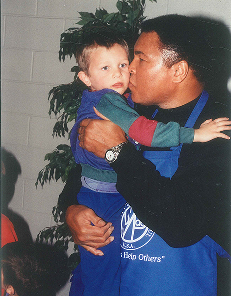 Boxing legend Muhammad Ali holds a child in SVdP's dining room.