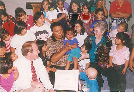 Boxing legend Muhammad Ali spends time with children in SVdP's dining room.