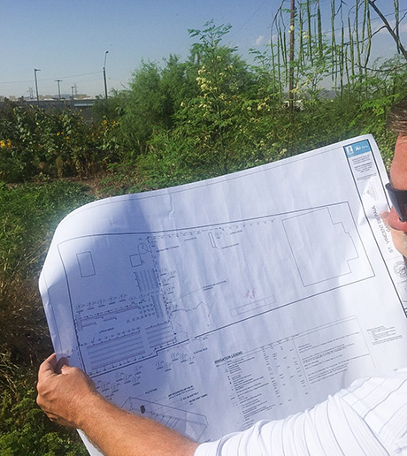 Creative Environments employee looks at irrigation system plans for SVdP's Urban Farm.