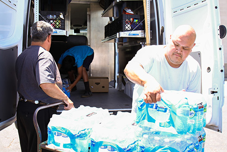 Joseph and Jose load the truck with bottled water.