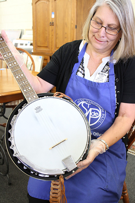 Josie inspects a banjo for resale online at the Mesa Thrift Store.