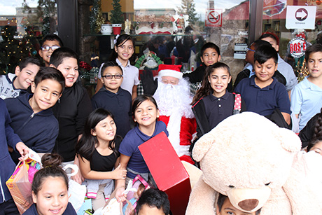Children pose for a photo with Santa at the Palomino Christmas event.