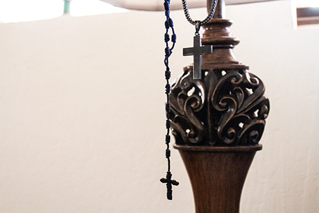 Rosary cross necklaces hang on a lamp in Richard's home.