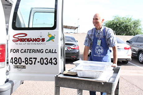 Ernie Serrano (Jr.) unloads food to serve during St. Vincent de Paul's lunch service in Mesa.