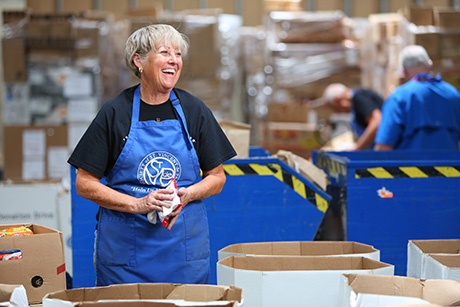 Volunteer sorts food in SVdP food warehouse.