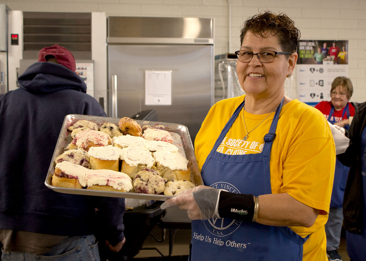 Mesa Dining Room Program Supervisor Carol Reed showcases a tray of Rise Up's donated baked goods.