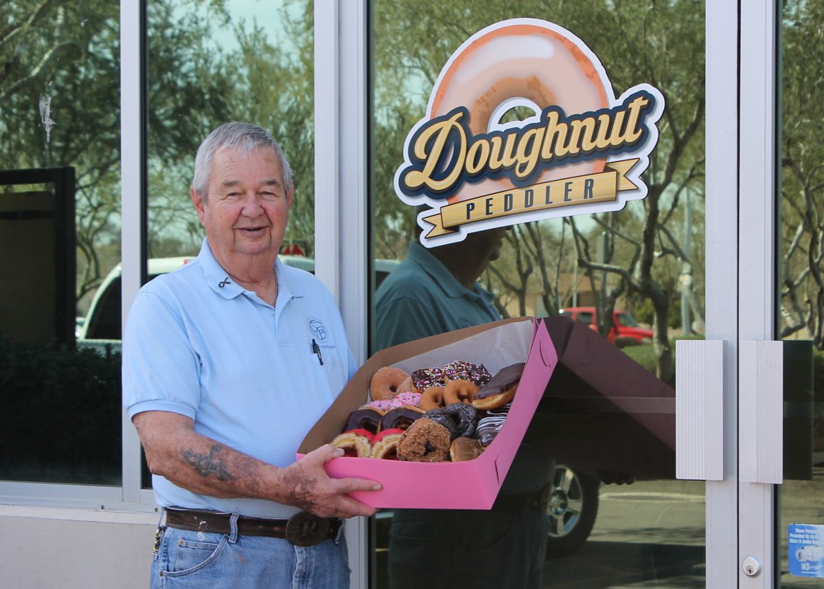 Vincentian volunteer Joe Rinker poses outside Doughnut Peddler with a variety box of doughnuts.