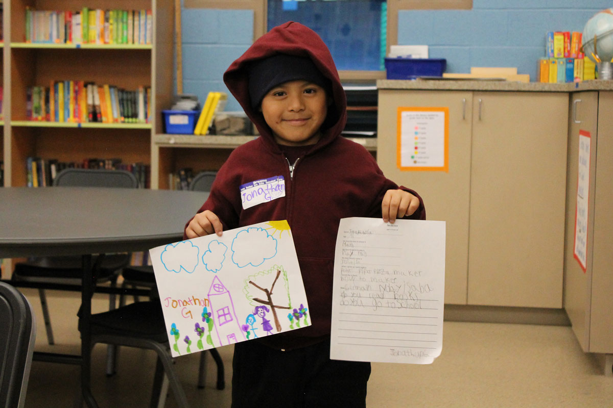 Dream Center student Jonathan, 8, holds up for display his letter and drawing to his Rwandan pen pal
